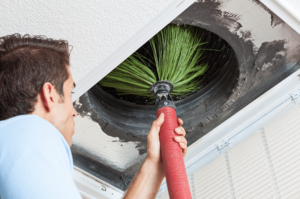 Technician cleaning an air duct